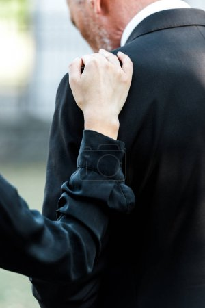 Photo pour Vue recadrée de la femme touchant l'homme sur les funérailles - image libre de droit