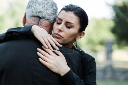 upset woman with closed eyes hugging senior man