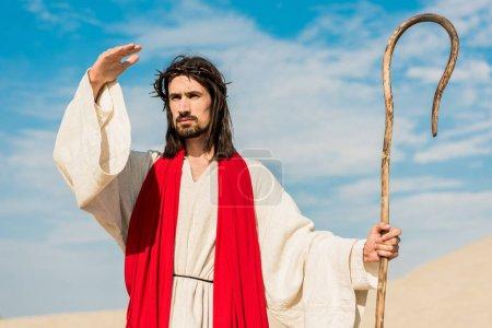 Photo pour Jésus barbu retenant la canne en bois contre le ciel bleu - image libre de droit