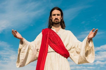 Photo for Bearded jesus with outstretched hands against blue sky - Royalty Free Image
