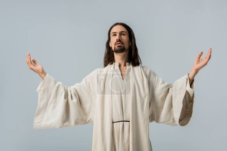 Photo pour Bel homme en robe de Jésus avec les mains tendues isolé sur gris - image libre de droit