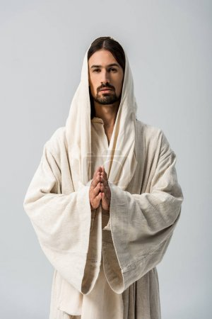 Photo for Religious man with praying hands and jesus robe with hood standing isolated on grey - Royalty Free Image
