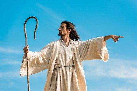 Photo pour Homme dans la robe de jésus retenant la canne en bois et pointant avec le doigt - image libre de droit