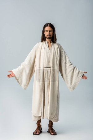 Photo for Religious man in jesus robe standing with outstretched hands on grey - Royalty Free Image