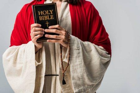 Photo pour Vue recadrée de l'homme tenant la bible sainte et chapelet pains isolés sur gris - image libre de droit