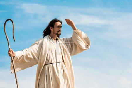 Photo pour Homme dans la canne de fixation de robe de jésus contre le ciel bleu - image libre de droit