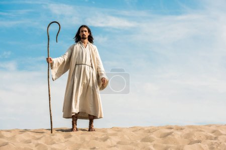 Photo for Handsome man in jesus robe holding wooden cane against blue sky in desert - Royalty Free Image