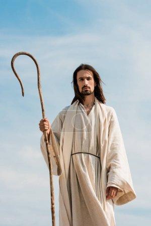 Photo pour Homme dans la robe de jésus retenant la canne en bois contre le ciel bleu dans le désert - image libre de droit