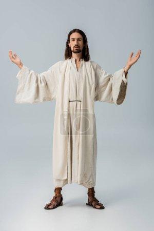 Photo pour Homme barbu dans la robe de jésus restant avec les mains tendues sur le gris - image libre de droit