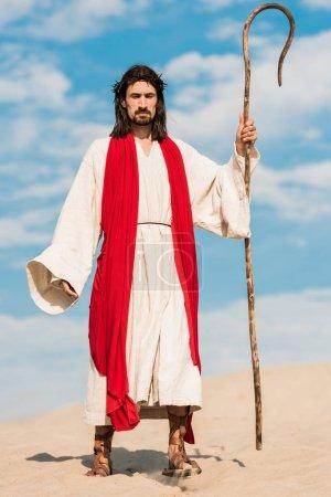 Photo pour Bel homme en robe de Jésus tenant une canne en bois et marchant dans le désert - image libre de droit