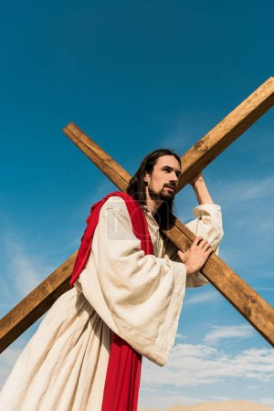 Photo pour Vue d'angle bas de Jésus retenant la croix contre le ciel bleu - image libre de droit