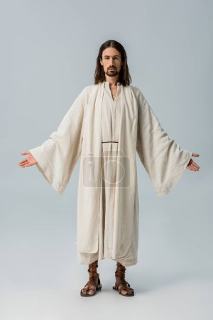 Photo for Handsome bearded man in jesus robe standing with outstretched hands on grey - Royalty Free Image