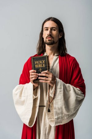Photo for Man holding rosary beads and holy bible and looking at camera isolated on grey - Royalty Free Image