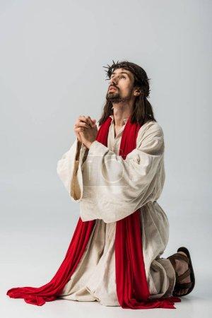 Photo pour Jésus dans la couronne priant sur des genoux sur le gris - image libre de droit