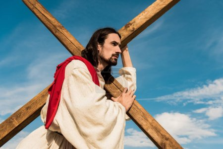 Photo pour Vue à angle bas de l'homme barbu tenant la croix contre le ciel bleu - image libre de droit