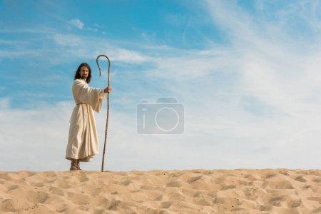 Photo pour Jésus retenant la canne en bois contre le ciel bleu dans le désert - image libre de droit