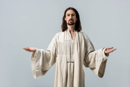 Photo for Religious man looking at camera and standing with outstretched hands isolated on grey - Royalty Free Image