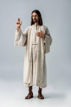 Photo pour Bel homme priant avec la main sur la poitrine sur le gris - image libre de droit