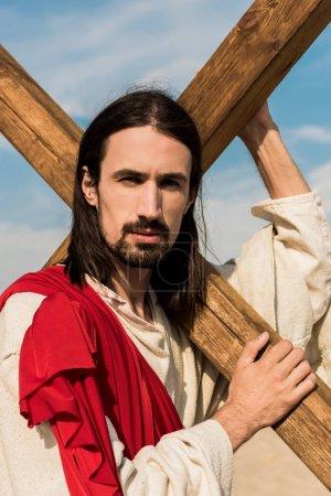 Photo pour Jésus barbu retenant la croix en bois et regardant l'appareil-photo - image libre de droit