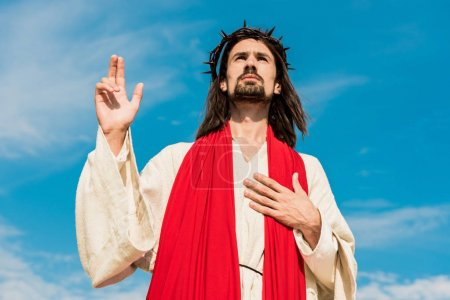 Photo for Low angle view of jesus praying with hand on chest - Royalty Free Image