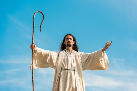 jesus with outstretched hands holding wooden cane against blue sky