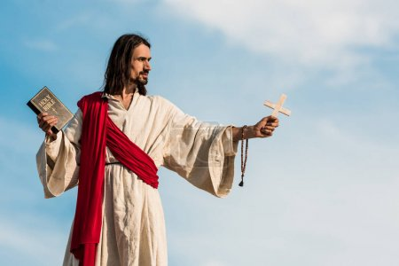 Photo for Jesus holding holy bible and cross against blue sky with clouds - Royalty Free Image