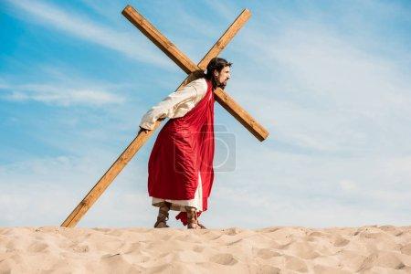 Photo pour Homme barbu en couronne marchant avec croix dans le désert - image libre de droit