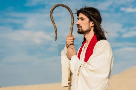 Photo for Handsome man in wreath holding wooden cane in desert - Royalty Free Image