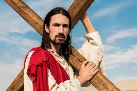 Photo pour Homme barbu retenant la croix en bois contre le ciel bleu - image libre de droit