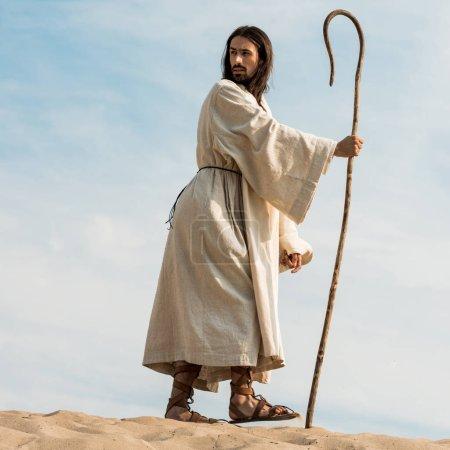Photo pour Vue bas d'angle de l'homme marchant avec la canne en bois dans le désert - image libre de droit