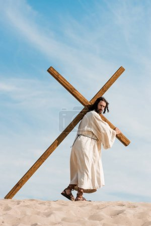 Photo for Jesus walking with wooden cross in desert - Royalty Free Image