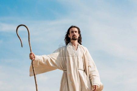 Photo pour Jésus tenant la canne en bois contre le ciel bleu et les nuages - image libre de droit