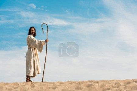 Photo pour Bel homme dans la robe de jésus retenant la canne en bois contre le ciel dans le désert - image libre de droit