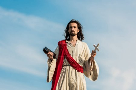 Photo for Jesus holding cross and holy bible against blue sky with clouds - Royalty Free Image
