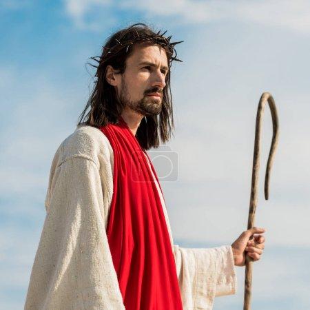 Photo pour Jésus dans la guirlande retenant la canne en bois à l'extérieur - image libre de droit