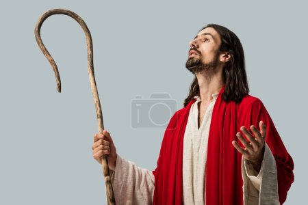 Photo pour Homme barbu dans la robe de jésus retenant la canne en bois et faisant des gestes isolés sur le gris - image libre de droit