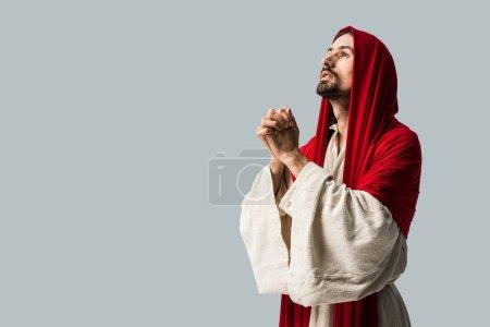 Photo pour Bel homme dans le capot rouge priant d'isolement sur le gris - image libre de droit