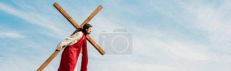 Photo pour Tir panoramique de l'homme barbu marchant avec la croix en bois - image libre de droit