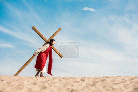 Photo pour Homme barbu marchant avec la croix en bois dans le désert - image libre de droit