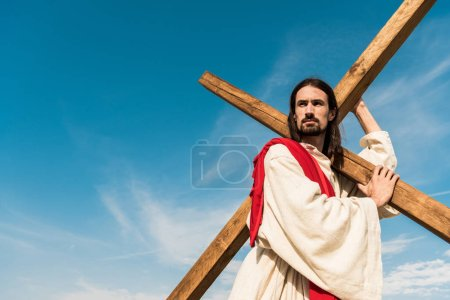 Photo for Low angle view of bearded jesus holding cross against sky with clouds - Royalty Free Image