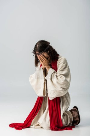 Photo for Jesus in wreath covering face while praying on knees on grey - Royalty Free Image