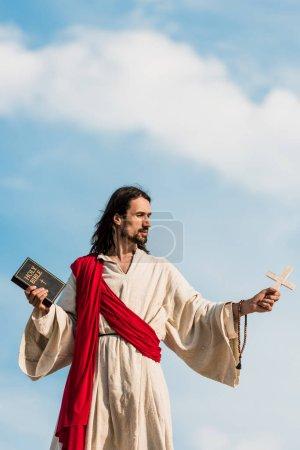 Photo pour Jésus retenant la bible sainte et la croix en bois contre le ciel bleu avec des nuages - image libre de droit
