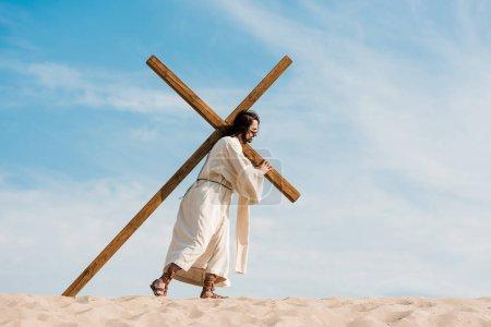 bearded man walking with wooden cross against sky in desert