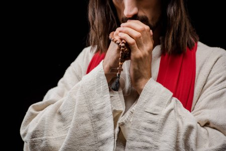 Photo for Cropped view of man holding rosary beads while praying isolated on black - Royalty Free Image