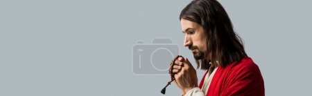 Photo for Panoramic shot of religious man holding rosary beads while praying isolated on grey - Royalty Free Image