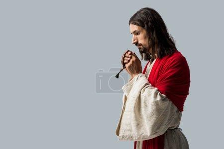 Photo pour Homme religieux retenant des perles de chapelet tout en priant isolé sur le gris - image libre de droit