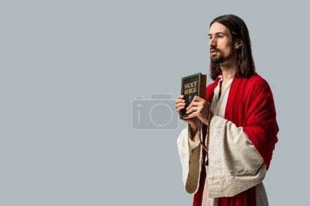 Photo pour Handsome bearded man holding holy bible isolated on grey - image libre de droit