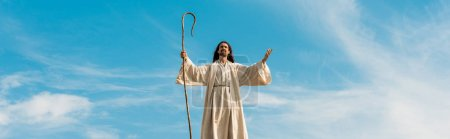 Photo pour Panoramic shot of jesus with outstretched hands holding wooden cane against sky - image libre de droit