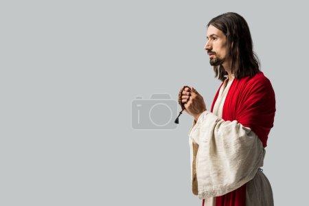 Photo for Jesus holding rosary beads while praying isolated on grey - Royalty Free Image