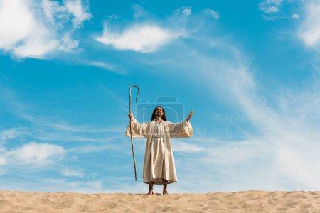 Photo pour Jésus avec les mains tendues retenant la canne en bois contre le ciel bleu dans le désert - image libre de droit